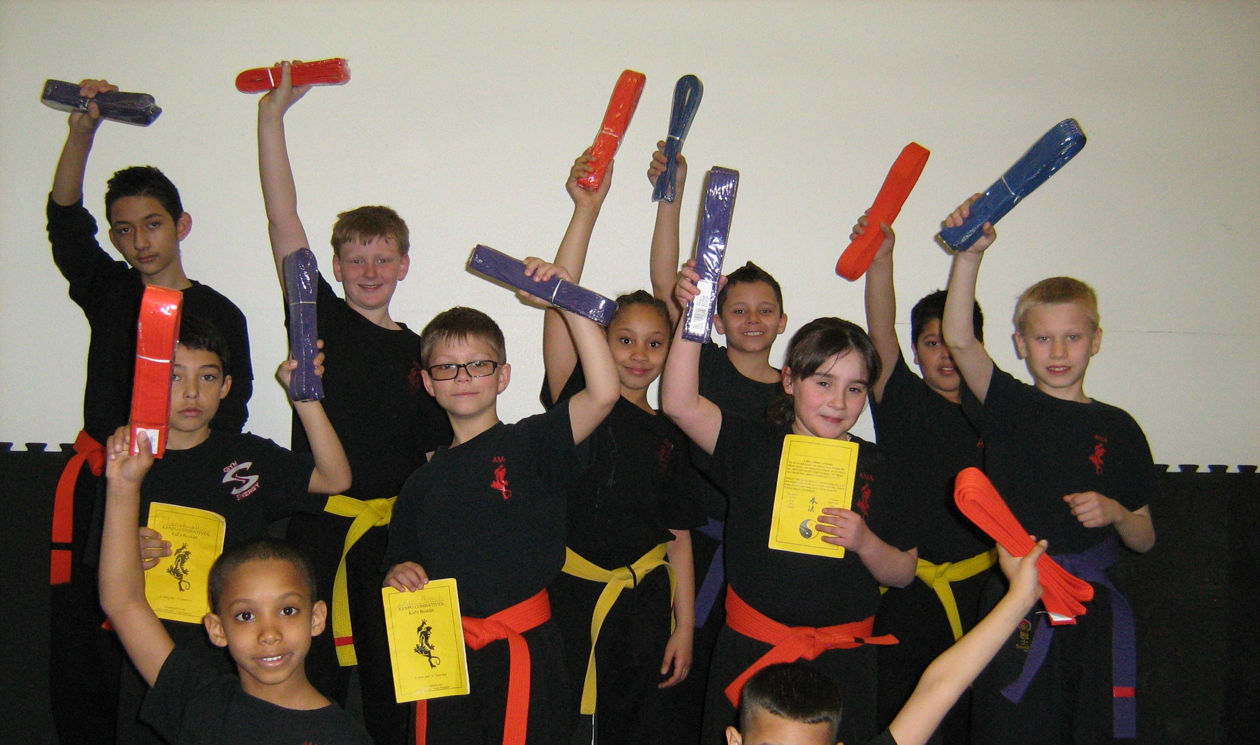 Kid's class students holding their new belts.